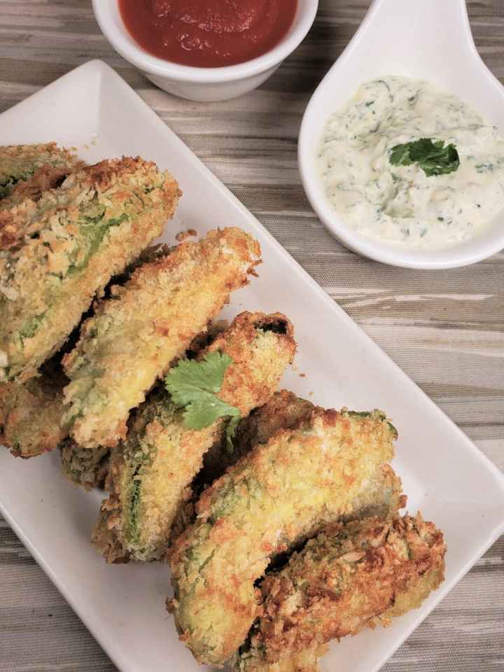 overhead sot of avocado fries on a rectangle plate, a dipped sauce in the back.