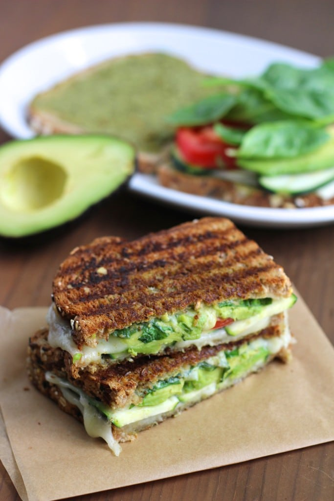 avocado grilled cheese on brown paper on a wood board.