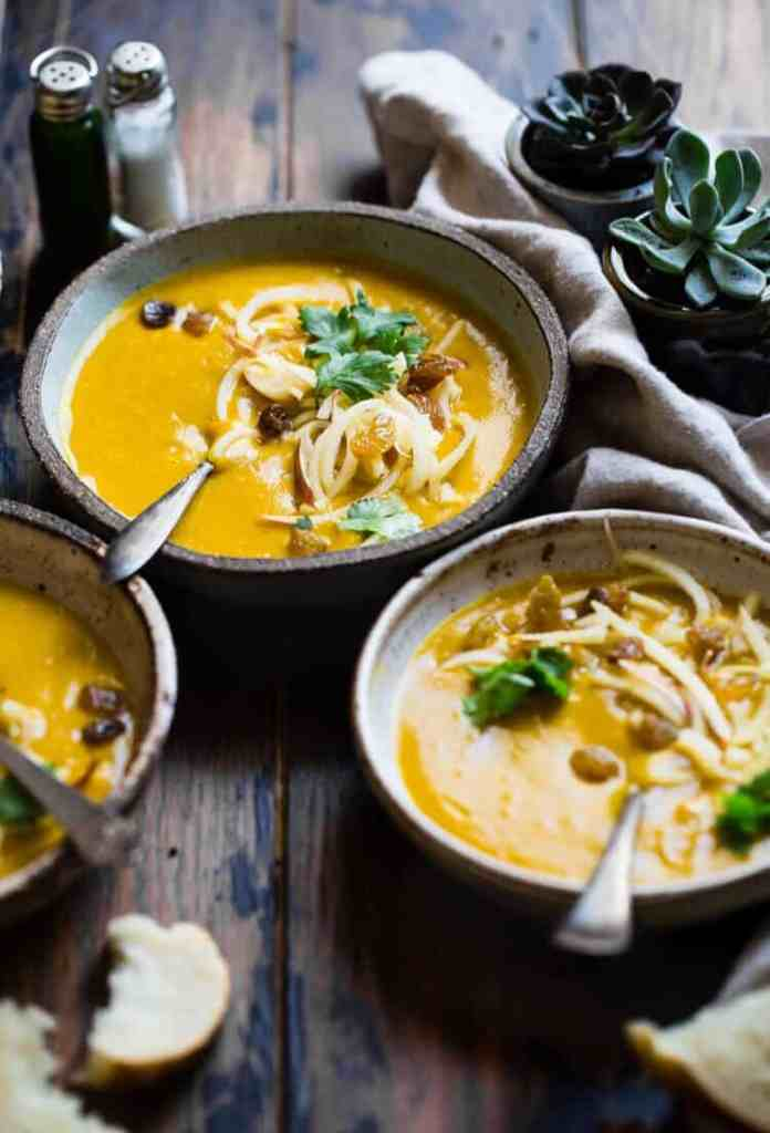 pumpkin soup in bowls on a dark wood surface