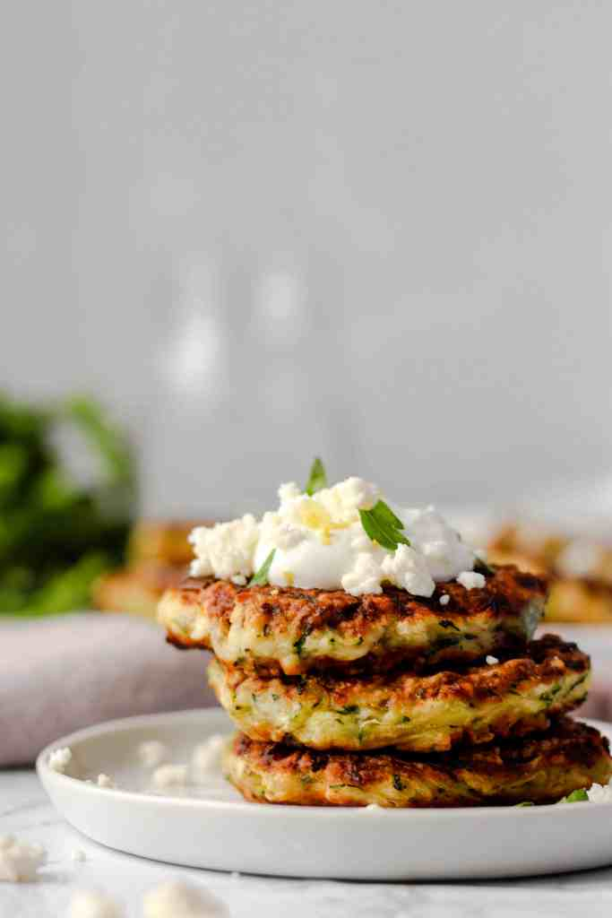 close shot of the 3 fritters on a round plate topped with Greek yogurt and feta and parsley and a little lemon zest.