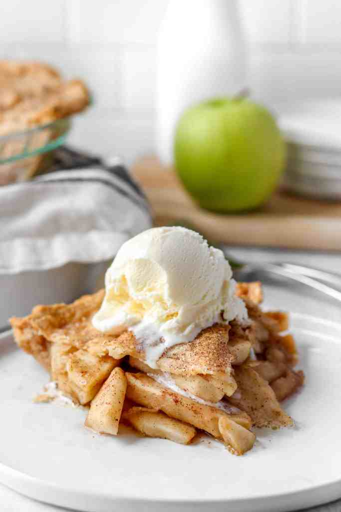 apple pie with a scoop of vanilla ice cream, the whole pie in the background.