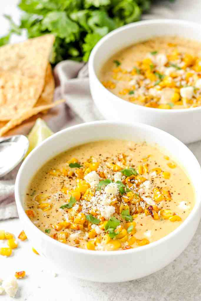 two bowls of creamy Mexican corn chowder with chips and parsley in the back.