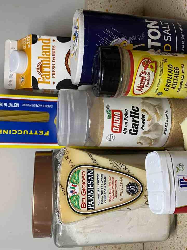 photo of packaged ingredients...flour, Parmesan cheese, fettuccine, garlic powder, garlic, ha;f & half, salt, pepper, nutmeg, butter.