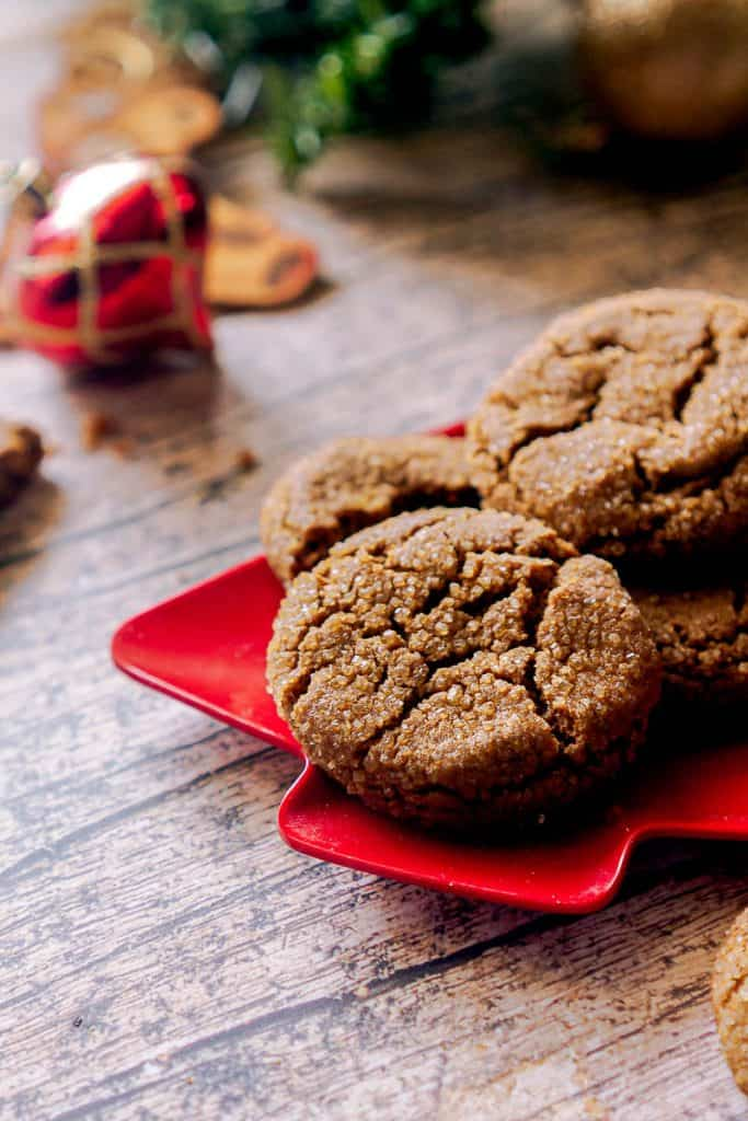 gingersnaps on a red plate with ornaments in the background.