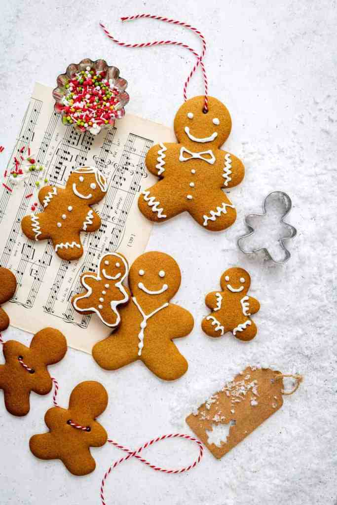 overhead shot of decorated gingerbread cookies on sheet music.