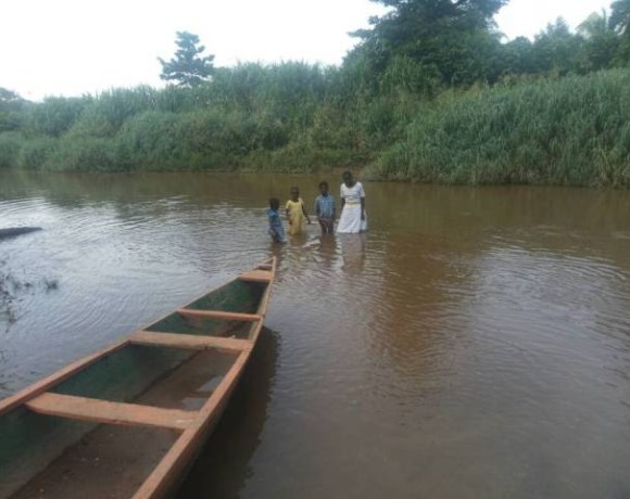 Some pupils crossing the Densu River to school..