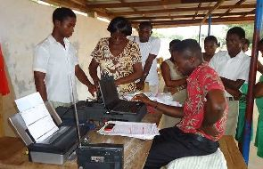 An EC official taking some residents through the registration process