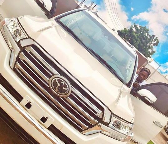 Shatta Wale poses with ride