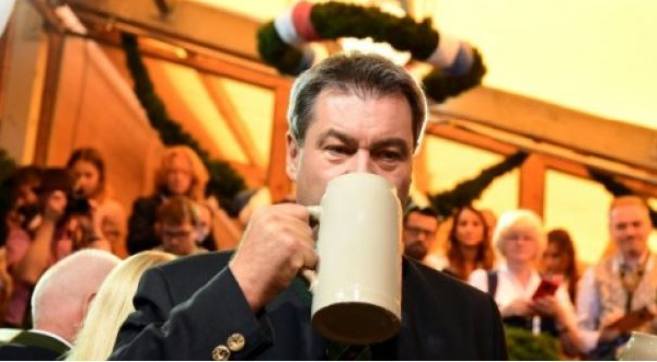 Bavaria's state premier Markus Soeder drinks beer from a stein