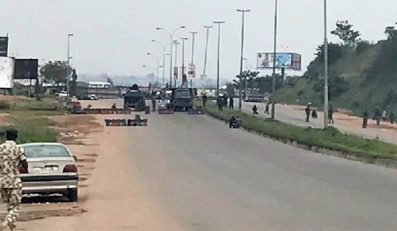 Nigerian forces block a road as IMN members march on the outskirts of Abuja