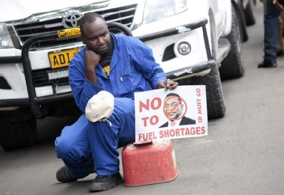 A mechanic with a placard written ' No to fuel prices'