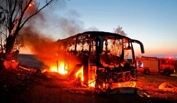 An empty bus in a kibbutz was set ablaze after being hit and an Israeli seriously wounded