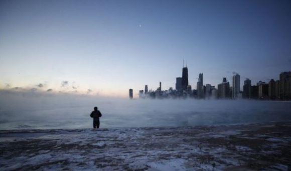 A man walks on North Avenue Beach as the sun rises over Lake Michigan in Chicago