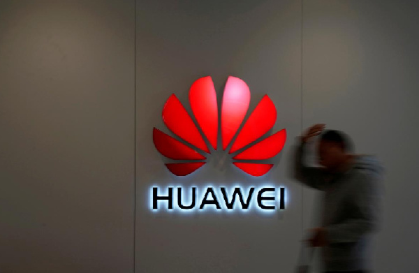 A man walks by a Huawei logo at a shopping mall in Shanghai, China