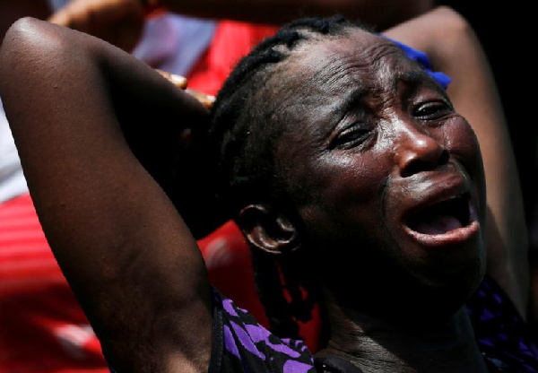A woman reacts at the site of a collapsed building containing a school in Nigeria