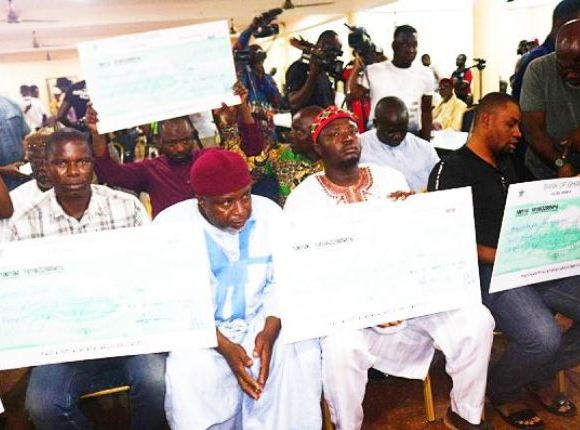 Relatives of the seven deaceased displaying their dummy cheques for GH¢250,000 each