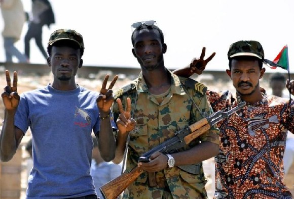 A Sudanese military officer and demonstrators gesture in celebration after Awad stepped down