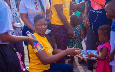 Salma Mumin giving out a pack of food to one of the children