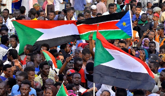 Sudanese demonstrators display their national flag and the national flag of South Sudan