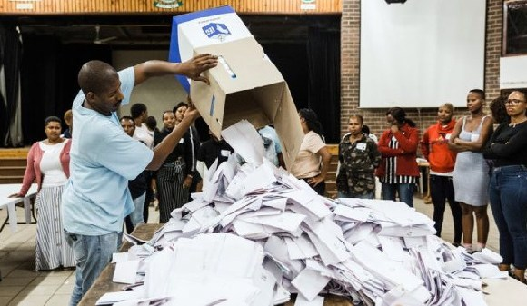 An election official empties a ballot box as counting begins in Durban