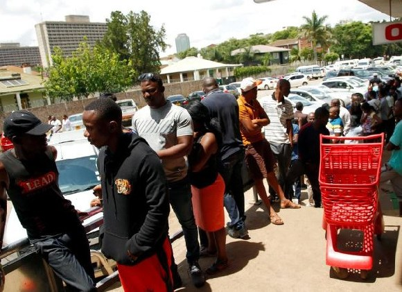 People queue to shop at a supermarket in Harare