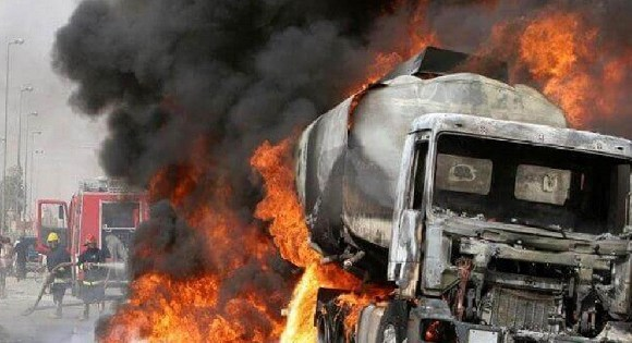Residents look at the tanker truck after a deadly explosion near the airport of Niamey on Monday