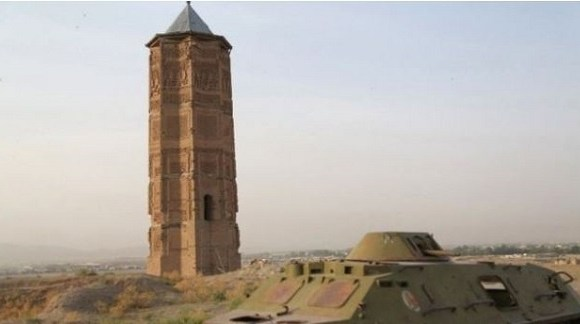 A destroyed Russian tank is seen alongside one of two minarets built in the 12th Century in Ghazni