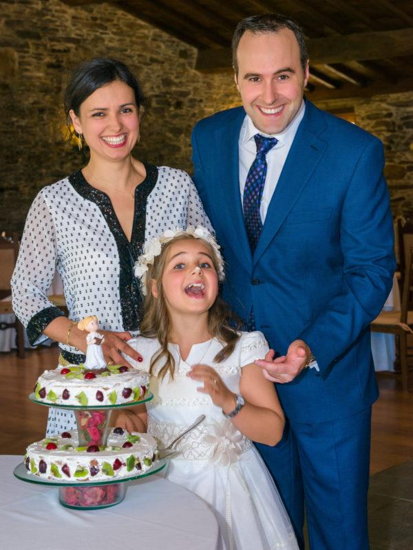 Fotografía de nena de comuñón, con papa e mama, cortando a tarta moi feliz