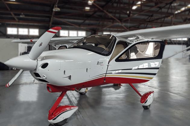 A white, red, gold, and black plane called the Tecnam P2008 with its doors open inside a plane hangar. Hire the Tecnam P2008