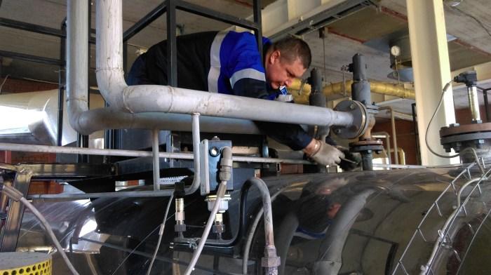 Специалист АСГАРД-Сервис проводит работы на котле заказчика