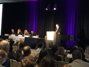 ASH 2018 Satellite Symposium Dr. Brian G.M. Durie at podium with panel of multiple myeloma experts