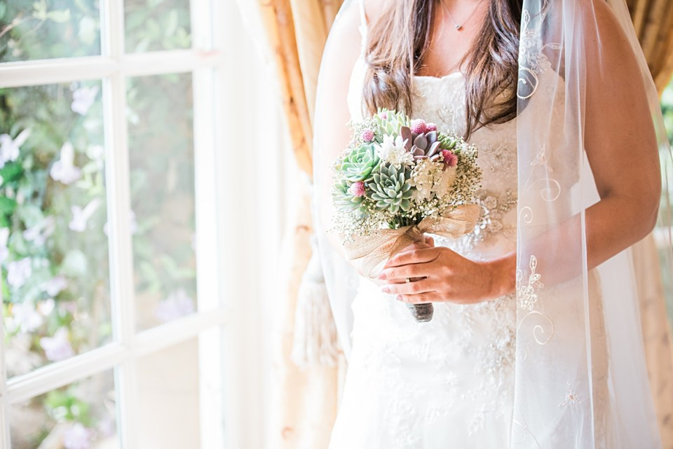 bride by window with succulent bouquet