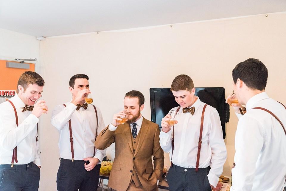 groom with groomsmen taking bourbon shots