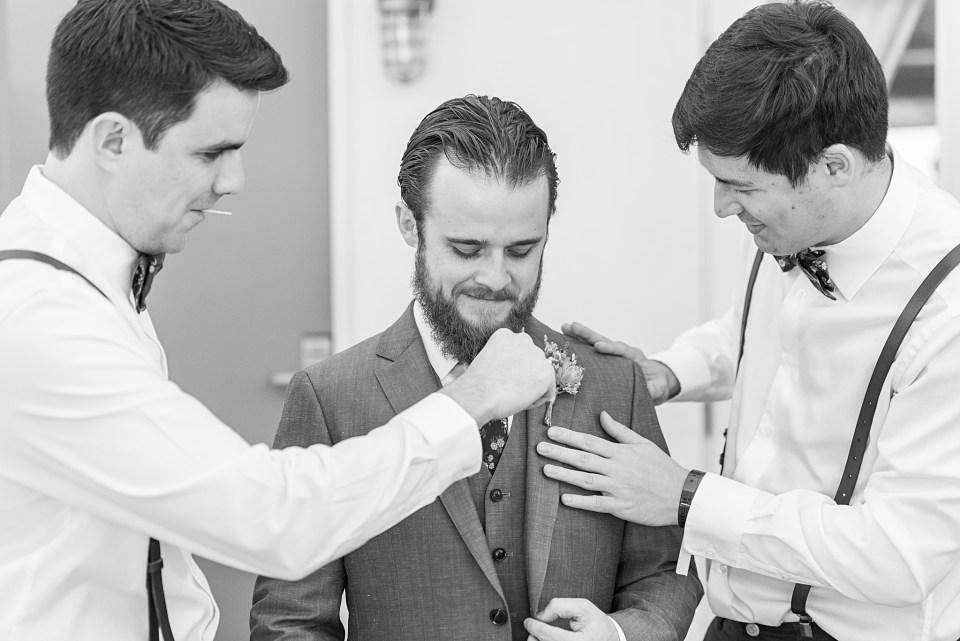 groomsmen helping groom get dressed
