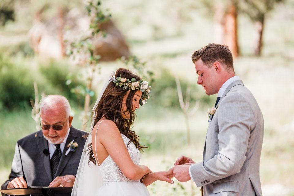 groom putting wedding ring on bride