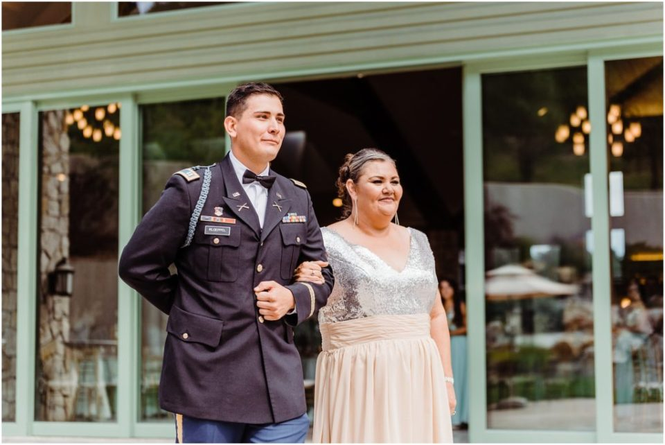 groom escorting his mother down the aisle at wedding ceremony