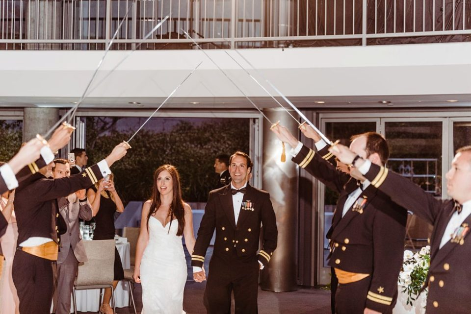 arch of sabers at navy wedding reception