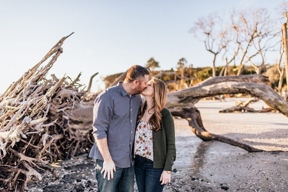 husband and wife kissing at driftwood beach