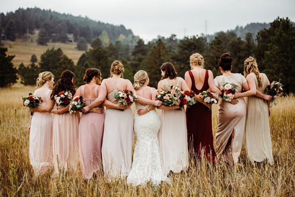 bridal party with arms wrapped around each other from behind