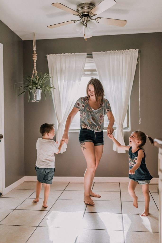 mom twirling her kids in the kitchen