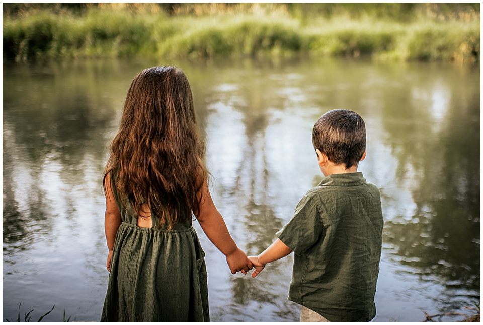 two kids holding hands next to the river