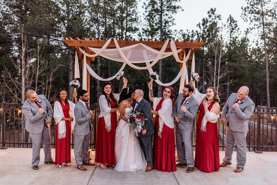 wedding party cheering on kissing newlyweds
