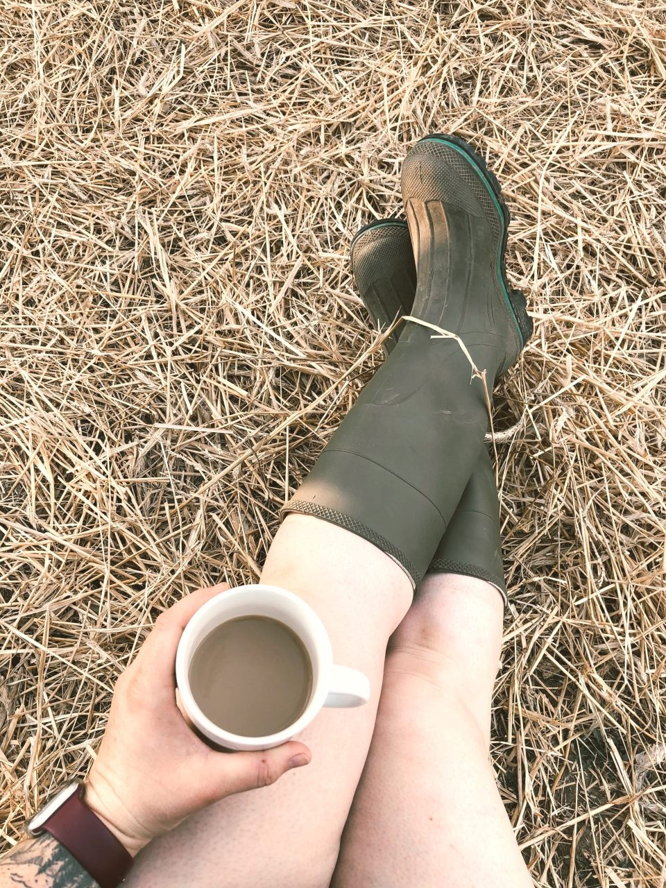 green rubber muck boots with a cup of coffee