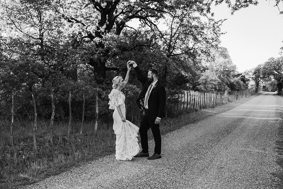 bride and groom dancing together on a texas dirt road