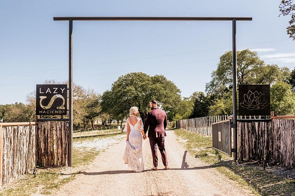 bride and groom walking down a dirt path at a texas ranch wedding