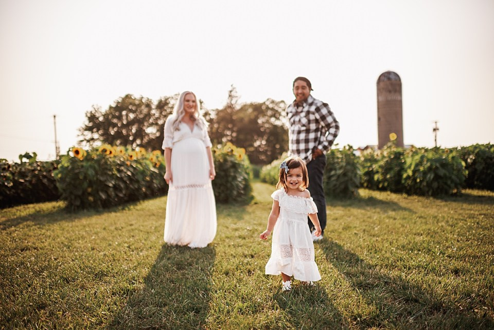 family of three in sunflower field