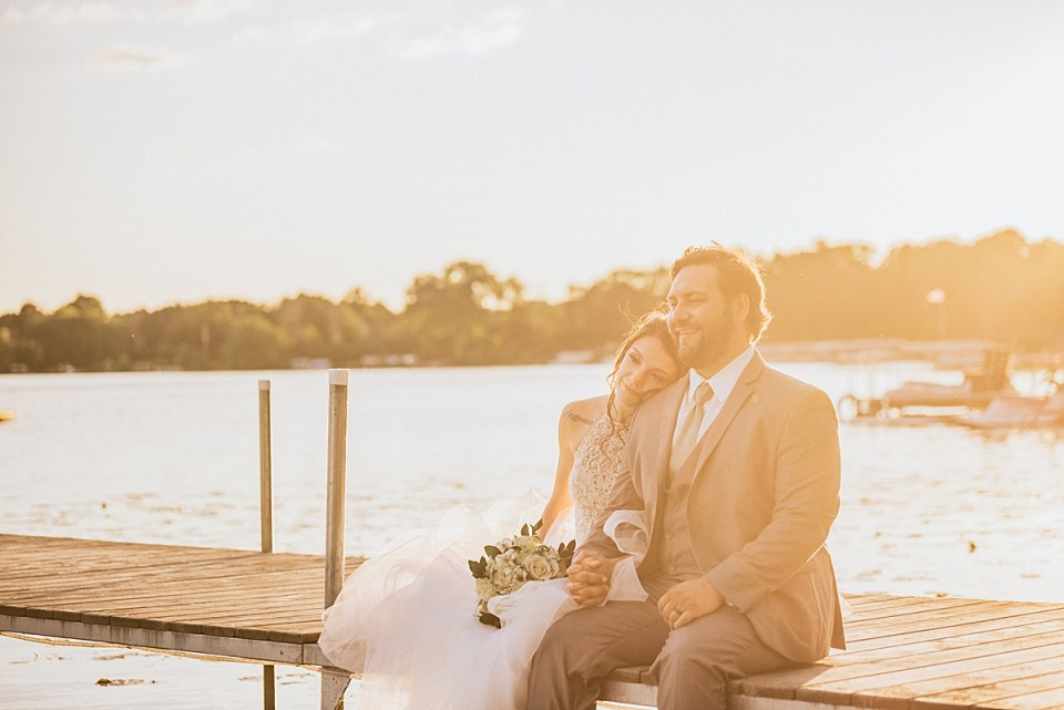 bride and groom sitting together on the pier at sunset