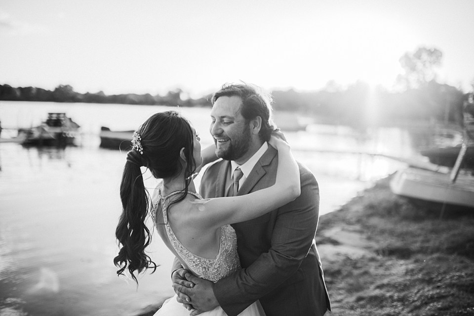 bride and groom in front of the lake at sunset