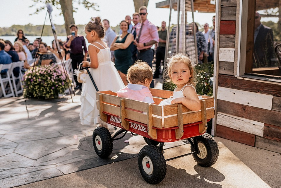 flower girl pulling ring bearer in a red wood wagon