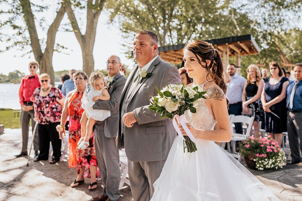 father of the bride walking bride down the aisle at outdoor ceremony